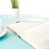 Books and pen on the blue table. flower, cup of coffee. Book, white background. Blue pen on the white notebook.